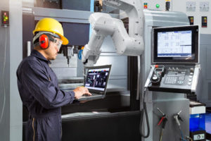 factory working using laptop to control cnc machine