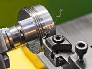 lathe spinning material around cutting it into desired shape