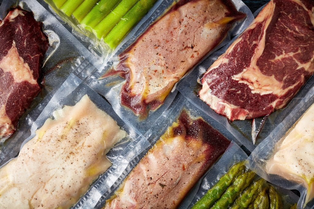 Meat and asparagus vacuum sealed on black table