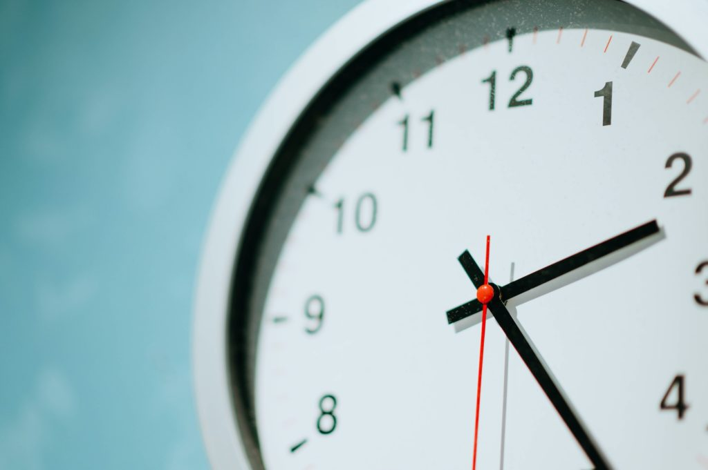 A close up picture of a white analog clock.