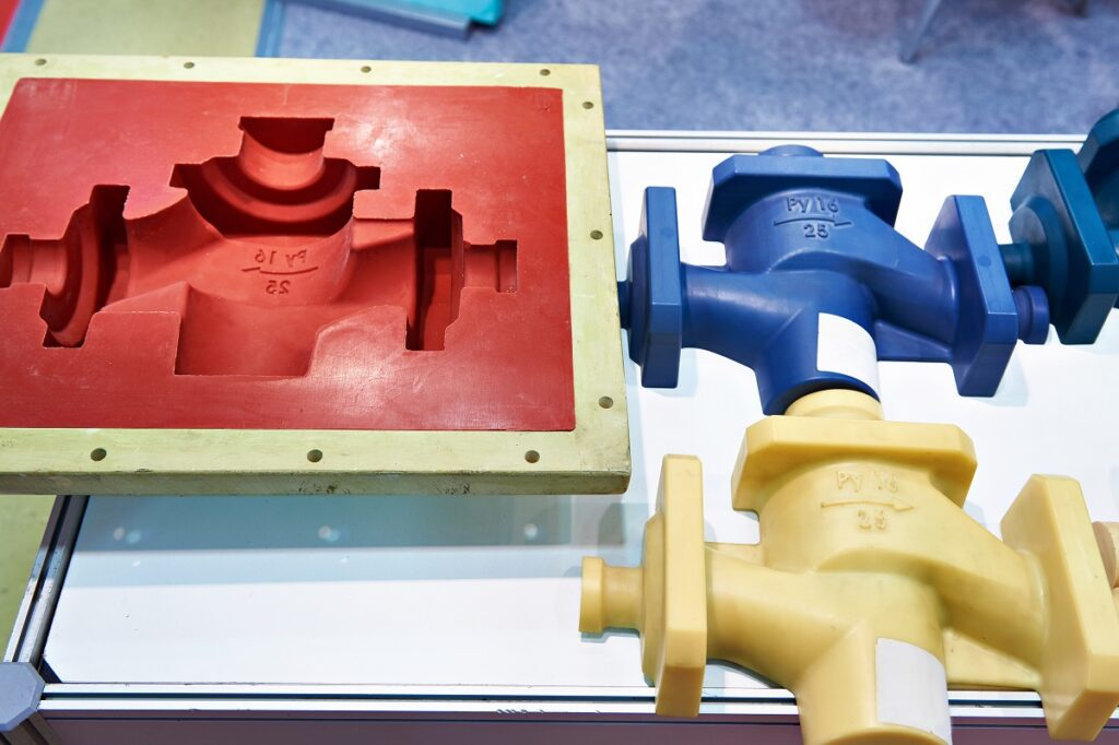A plastic injection mold next to two product samples