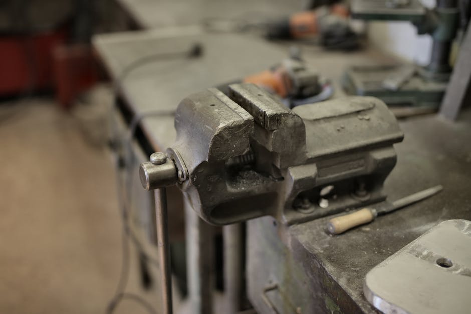 Metal vise and assorted tools in workshop